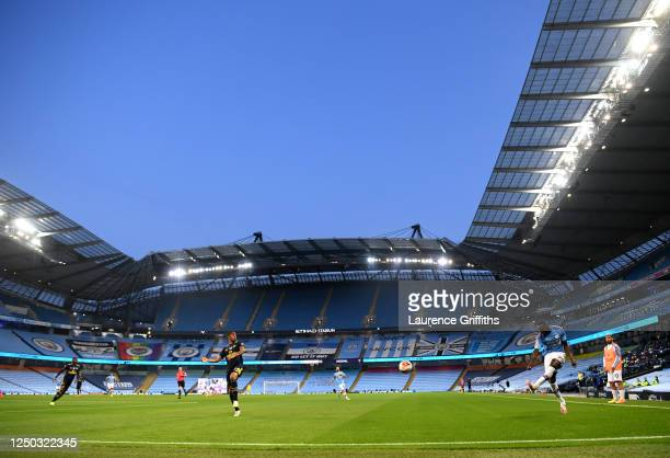 Benjamin Mendy of Manchester City crosses the ball under pressure from Reiss Nelson of Arsenal during the Premier League match between Manchester...
