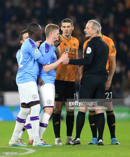 Benjamin Mendy of Manchester City hands an object thrown onto the pitch from the stands to Referee Martin Atkinson during the Premier League match...