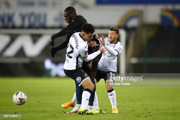 Benjamin Mendy of Manchester City is challenged by Joel Latibeaudiere and Paul Arriola of Swansea City during The Emirates FA Cup Fifth Round match...