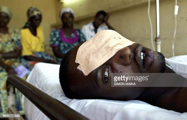 Benjamin Mugabe lies on his bed as his relatives visit him while recovering at Bujumbura hospital, 15 August 2004, after they were attacked, 14...