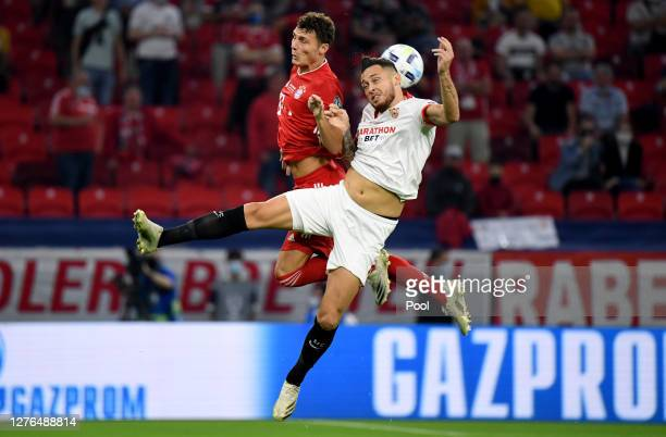Benjamin Pavard of Bayern Munich and Lucas Ocampos of Sevilla FC jump for a header during the UEFA Super Cup match between FC Bayern Munich and FC...
