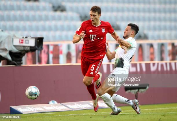 Benjamin Pavard of Bayern Munich is challenged by Ramy Bensebaini of Borussia Monchengladbach during the Bundesliga match between FC Bayern Muenchen...