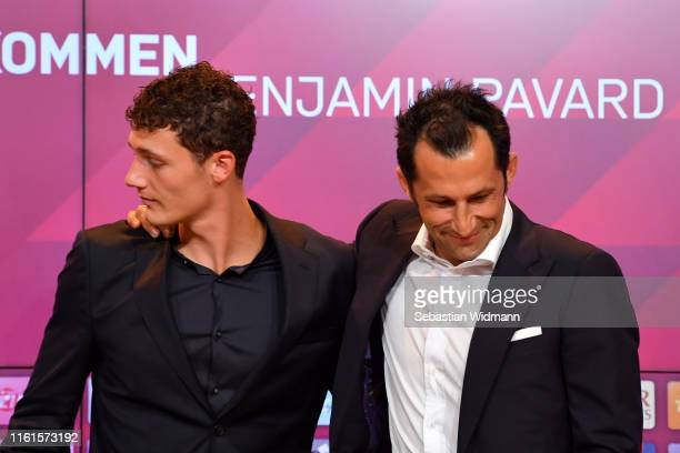 Benjamin Pavard of FC Bayern Muenchen and Hasan Salihamidzic sporting director of FC Bayern Muenchen hug at the end of a press conference to announce...