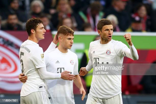 Benjamin Pavard of FC Bayern Munich celebrates after scoring his team's first goal with Thomas Muller and Joshua Kimmich during the Bundesliga match...
