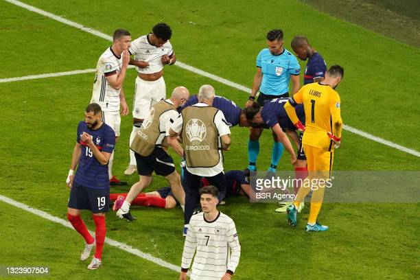 Benjamin Pavard of France receiving medical treatment during the UEFA Euro 2020 match between France and Germany at Allianz Arena on June 15, 2021 in...