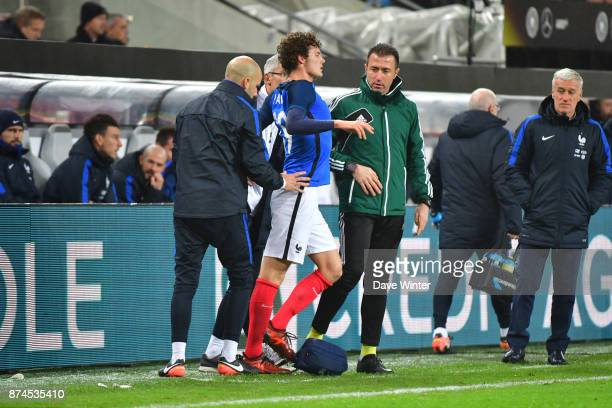 Benjamin Pavard of France us treated by France team doctor Franck Le Gall as France coach Didier Deschamps looks on during the international friendly...