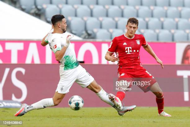 Benjamin Pavard of Muenchen is challenged by Ramy Bensebaini of Moenchengladbach during the Bundesliga match between FC Bayern Muenchen and Borussia...