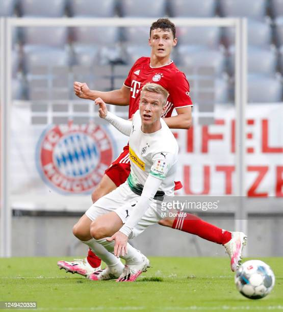 Benjamin Pavard of Muenchen passes the ball past Oscar Wendt of Moenchengladbach to assist teammate Leon Goretzka scoring his team's second goal...