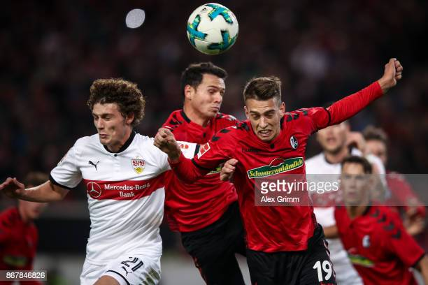 Benjamin Pavard of Stuttgart Nicolas Hoefler and Janik Haberer of Freiburg jump for a header during the Bundesliga match between VfB Stuttgart and...