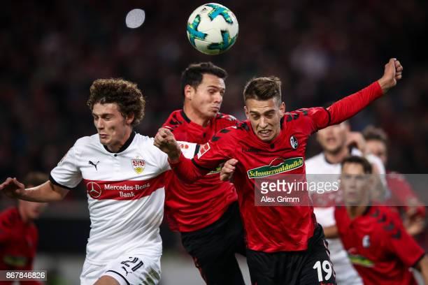 Benjamin Pavard of Stuttgart Nicolas Hoefler and Janik Haberer of Freiburg jump for a header during the Bundesliga match between VfB Stuttgart and...
