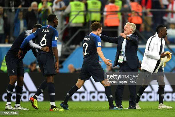 Benjamin Pavard Paul Pogba Presnel Kimpembe and manager Didier Deschamps of France celebrate victory following the 2018 FIFA World Cup Russia Semi...