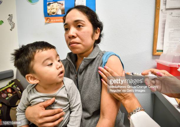 Benjamin Paz keeps an eye on his mom Dominga Vanessa Xirum as she gets a flu shot at the Orange County Health Care Agency in Santa Ana on Thursday...