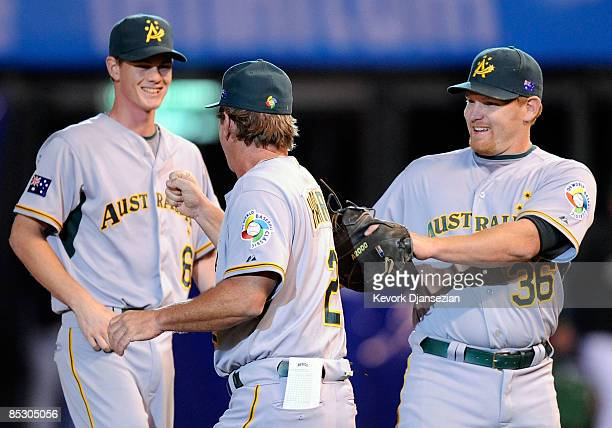 Benjamin Risinger of Australia celebrates their, 17-7, win over Mexico with third base coach Tony Harris and James Beresford during the 2009 World...