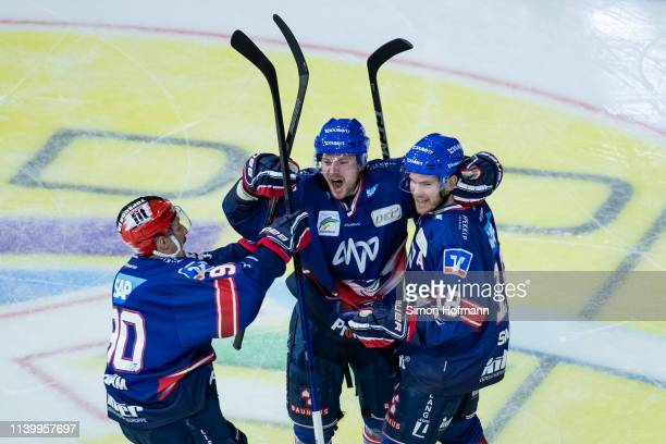 Benjamin Schmid of Mannheim celebrates his team's first goal with team mates Tommi Huhtala and Luke Adam during game one of the DEL PlayOffs Semi...