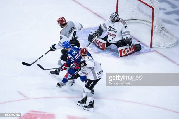 Benjamin Schmid of Mannheim scores his team's first goal against Goalkeeper Hannibal Weitzmann of Koeln during game one of the DEL PlayOffs Semi...