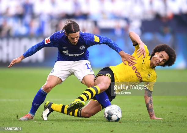 Benjamin Stambouli of FC Schalke 04 battles for possession with Axel Witsel of Borussia Dortmund during the Bundesliga match between FC Schalke 04...