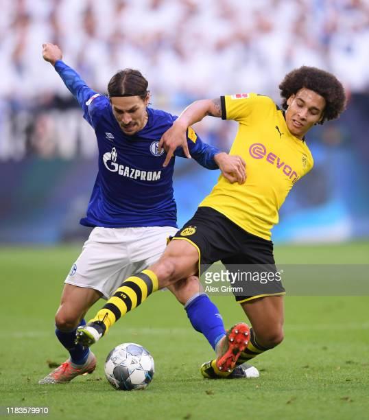 Benjamin Stambouli of FC Schalke 04 battles for possession with Axel Witsel of Borussia Dortmund during the Bundesliga match between FC Schalke 04...