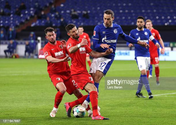 Benjamin Stambouli of FC Schalke 04 is challenged by Mads Pedersen of FC Augsburg during the Bundesliga match between FC Schalke 04 and FC Augsburg...