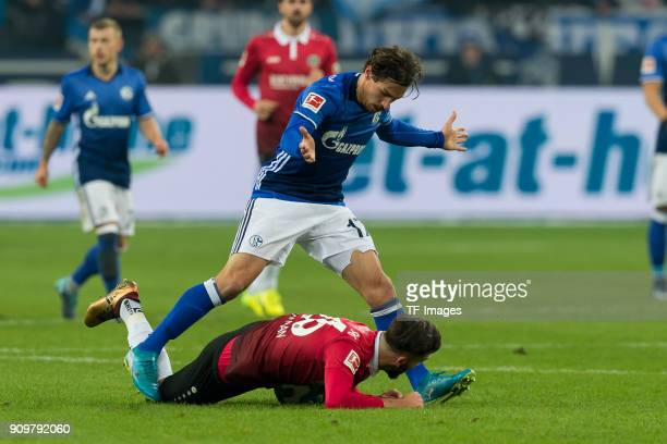 Benjamin Stambouli of Schalke and Kenan Karaman of Hannover battle for the ball during the Bundesliga match between FC Schalke 04 and Hannover 96 at...