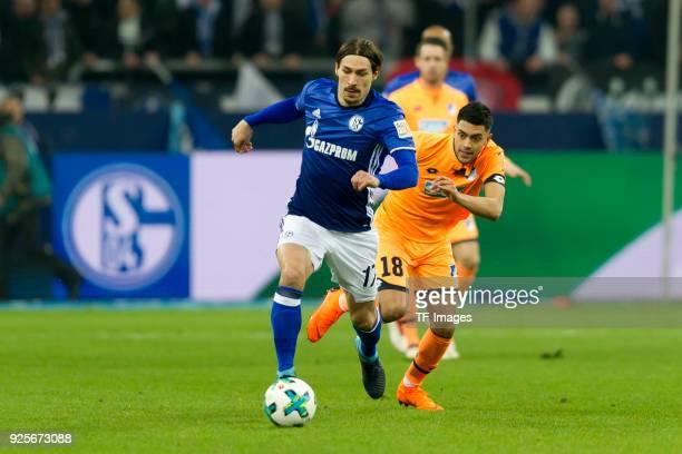 Benjamin Stambouli of Schalke and Nadiem Amiri of Hoffenheim battle for the ball during the Bundesliga match between FC Schalke 04 and TSG 1899...
