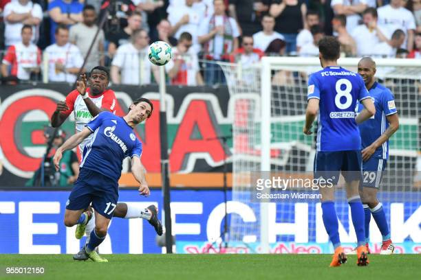 Benjamin Stambouli of Schalke and Sergio Cordova of Augsburg compete for the ball during the Bundesliga match between FC Augsburg and FC Schalke 04...