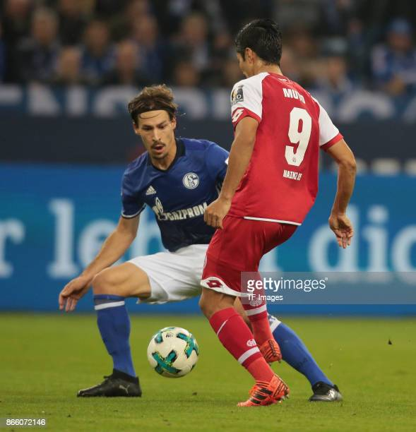 Benjamin Stambouli of Schalke and Yoshinori Muto of Mainz battle for the ball during the Bundesliga match between FC Schalke 04 and 1 FSV Mainz 05 at...
