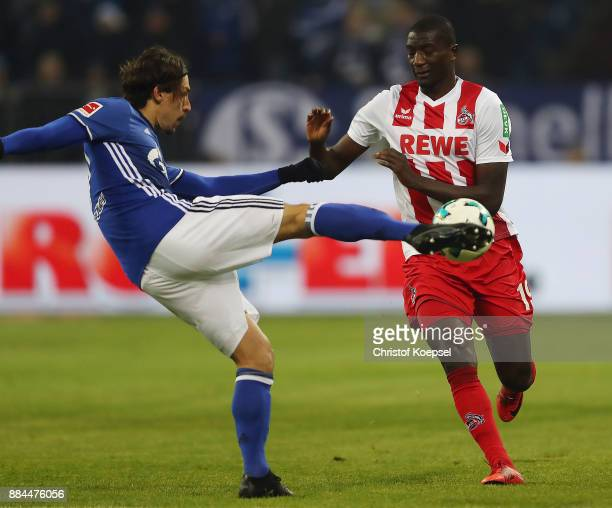 Benjamin Stambouli of Schalke fights for the ball with Sehrou Guirassy of Koeln during the Bundesliga match between FC Schalke 04 and 1 FC Koeln at...