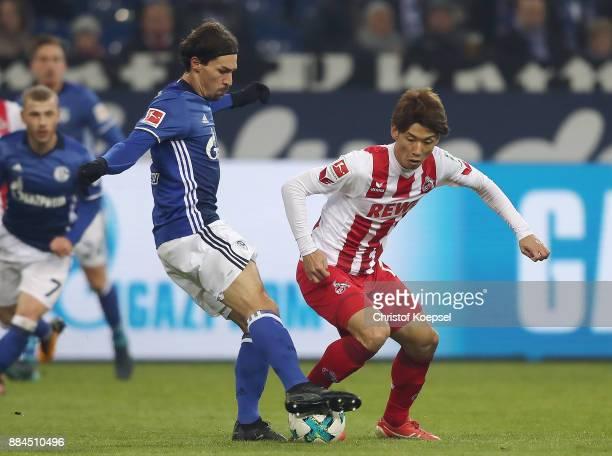 Benjamin Stambouli of Schalke fights for the ball with Yuya Osako of Koeln during the Bundesliga match between FC Schalke 04 and 1 FC Koeln at...