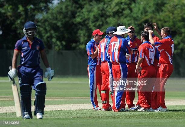 Benjamin Stevens of Jersey celebrates a wicket with team mates during the European Division 1 Championship Group B match between Jersey and France at...