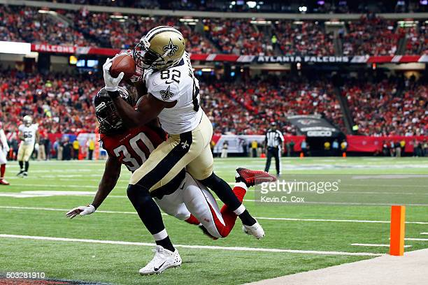 Benjamin Watson of the New Orleans Saints scores a touchdown over Charles Godfrey of the Atlanta Falcons during the first half at the Georgia Dome on...