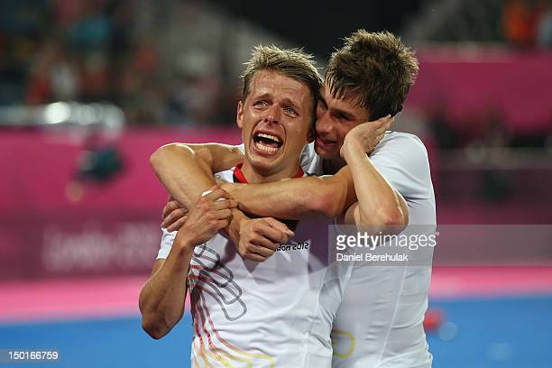 Benjamin Wess of Germany is comforted by a team mate while celebrating winning the gold medal against Netherlands in the Men's Hockey gold medal...