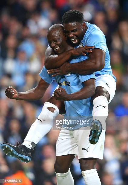 Benjani of Manchester City Legends celebrates with team mate Micah Richards after scoring a goal during the Vincent Kompany testimonial match between...