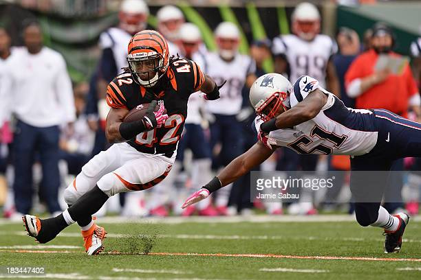 BenJarvus Green-Ellis of the Cincinnati Bengals breaks a tackle attempt from Jerod Mayo of the New England Patriots in the first quarter while...