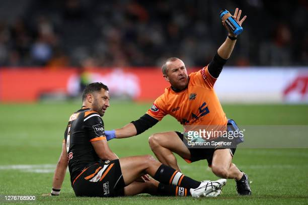 Benji Marshall of the Tigers is attended to by a trainer after a tackle during the round 20 NRL match between the Wests Tigers and the Parramatta...