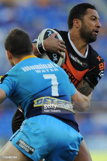 Benji Marshall of the Tigers is tackled during the round 21 NRL match between the Gold Coast Titans and the Wests Tigers at Skilled Park on August 4...