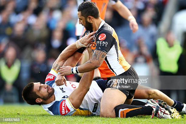 Benji Marshall of the Tigers punches James Tamou of the Cowboys after a suspected late tackle during the round 12 NRL match between the Wests Tigers...
