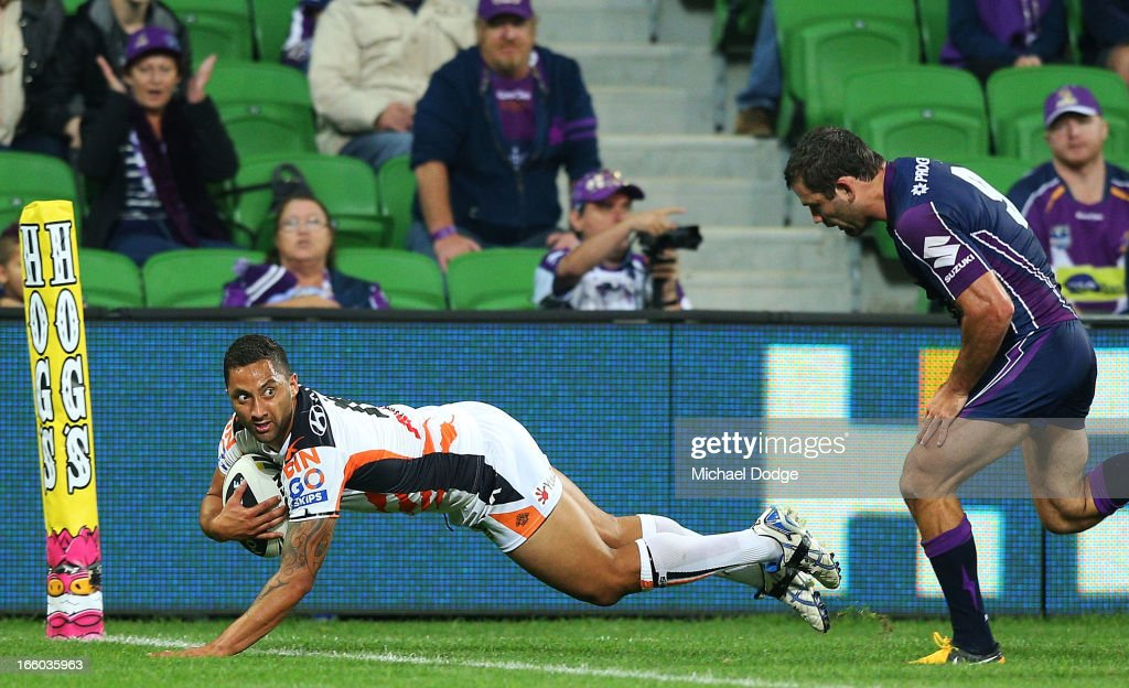 Benji Marshall of the Tigers scores a try past Cameron Smith of the Storm during the round 5 NRL match between the Melbourne Storm and the Wests Tigers at AAMI Stadium on April 8, 2013 in Melbourne, Australia.