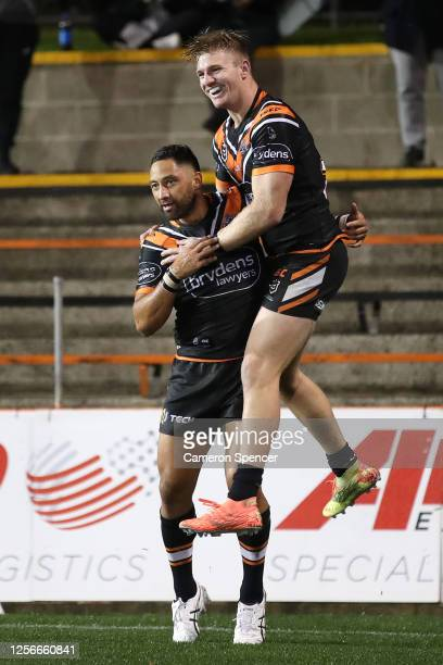 Benji Marshall of the Wests Tigers is congratulated by team mates after scoring a try during the round 10 NRL match between the Wests Tigers and the...