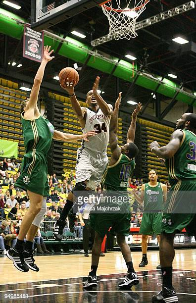 Bennet Davis of the Utah Flash lays up a shot against Cezary Trybanski and Dave Noel of the Reno Bighorns during the D-League game on December 11,...