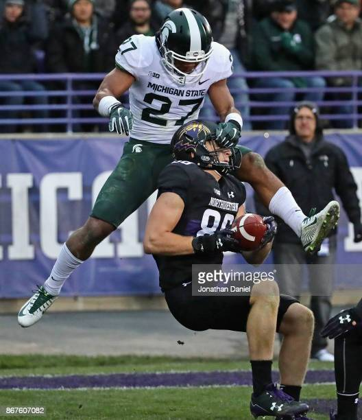 Bennett Skowronek of the Northwestern Wildcats is grabbed by the face mask after making a touchdown catch by Khari Willis of the Michigan State...
