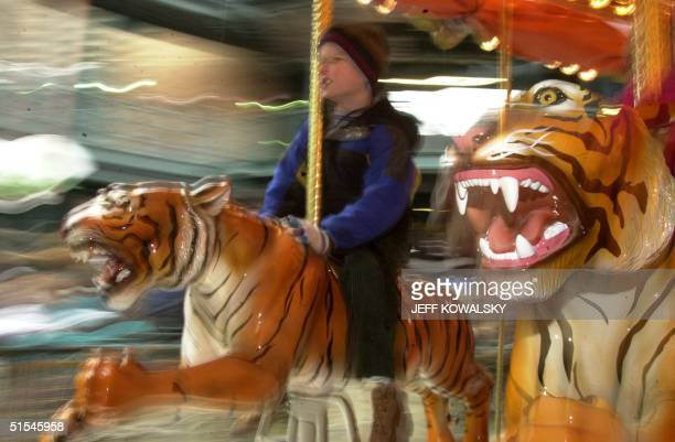 Bennett Weckler of Traverse City Michigan rides the carousel that is part of the Detroit Tigers' new home Comerica Park in Detroit 11 April 2000 The...