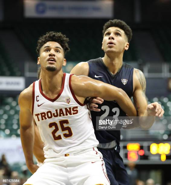 Bennie Boatwright of the USC Trojans and Jaden Sayles of the Akron Zips battle for position under the basket during the first half of their game at...
