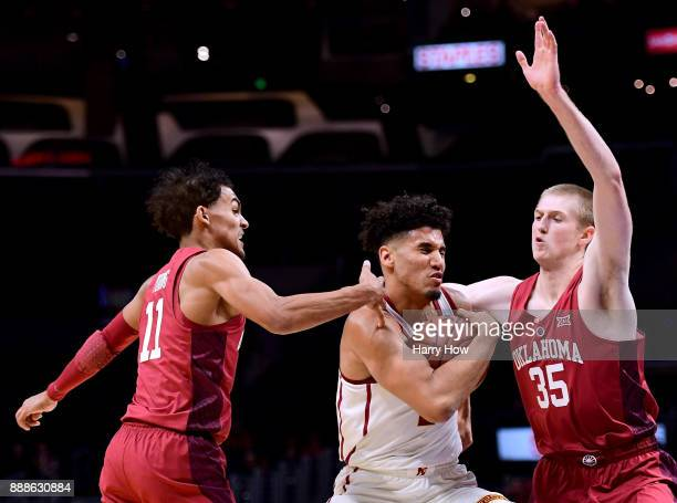 Bennie Boatwright of the USC Trojans drives between Trae Young and Brady Manek of the Oklahoma Sooners during the Basketball Hall of Fame Classic at...