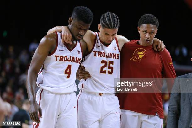 Bennie Boatwright of the USC Trojans gets helped off the court by team mates Chimezie Metu and Harrison Henderson after injuring knee against Oregon...
