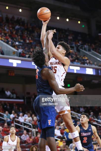 Bennie Boatwright of the USC Trojans handles the ball against Davon Clare of the CalState Fullerton Titans during a college basketball game at Galen...