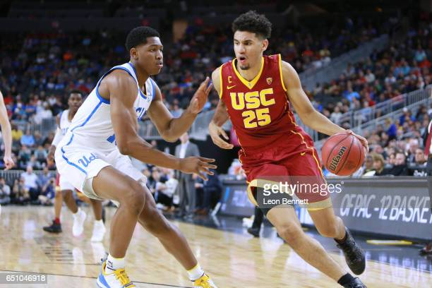 Bennie Boatwright of the USC Trojans handles the ball against Ike Anigbogu of the UCLA Bruins during a quarterfinal game of the Pac12 Basketball...