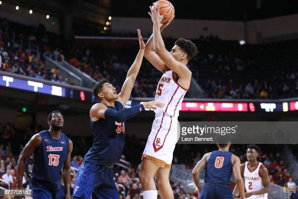 Bennie Boatwright of the USC Trojans handles the ball against Jackson Rowe of the CalState Fullerton Titans during a at Galen Center on November 10...