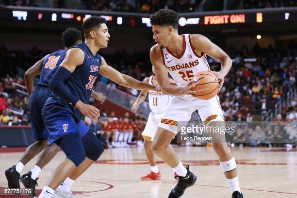 Bennie Boatwright of the USC Trojans handles the ball against Jackson Rowe of the CalState Fullerton Titans during a college basketball game at Galen...