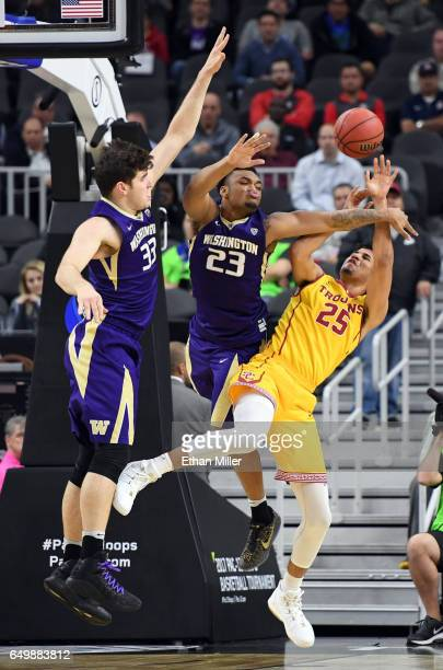 Bennie Boatwright of the USC Trojans is fouled as he goes to the basket against Sam Timmins and Carlos Johnson of the Washington Huskies during a...