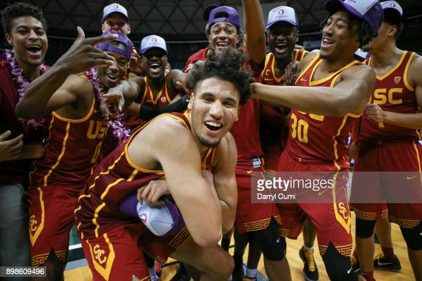 Bennie Boatwright of the USC Trojans poses with his teammates after winning the championship game of the Diamond Head Classic against the New Mexico...
